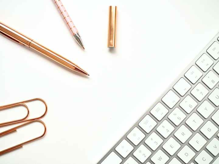 pens near keyboard and paper clips